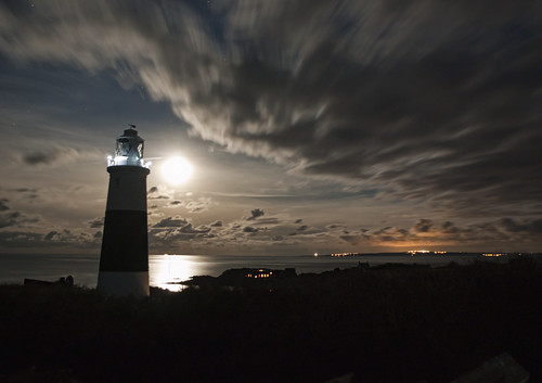 Alderney's Lighthouse overlooking the French coast under a full Moon