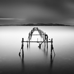 almost infinity (Julia-Anna Gospodarou) Tags: longexposure sunset sea bw white seascape black mountains water clouds pier nikon metallic jetty smooth athens le serene af tamron deserted decaying silky 2012 manfrotto hoya nd400 quiteness nd8 aspropyrgos sirui 055xprob 18270mm nikond7000 k20x 3563pzd