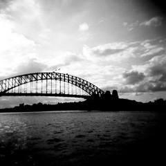 Sydney Harbour Bridge (Kerrie McSnap) Tags: bridge sky blackandwhite bw 120 film clouds mediumformat square blackwhite holga lomo lomography kodak harbour tmax toycamera sydney grainy sydneyharbourbridge