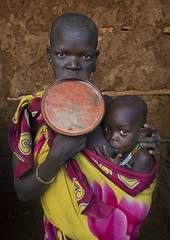 Suri Tribe Woman With A Lip Plate And Her Baby, Kibish, Omo Valley, Ethiopia (Eric Lafforgue) Tags: africa portrait people baby color love beauty vertical wall proud outside photography interesting colorful day serious outdoor body decoration mother bald culture pride jewelry tribal ornament clay adobe intriguing omovalley breastfeeding tradition ethiopia tribe pastoral shavedhead ethnic groupofpeople surma bizarre impressive bodymodification jewel labret confidence hornofafrica individuality ethnology omo eastafrica suri img0763 traditionalclothing realpeople colorimage biglip lookingatcamera beautify waistup africanethnicity pastoralist pastoralism lipplug lipplate stretchedlip kibish snnpr bodytransformation lipdisc southernnationsnationalitiesandpeoplesregion kibbish piercedhole piercedlipornament ethiopianethnicity
