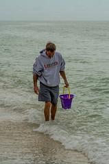 Grim Seashell Hunter (pruse) Tags: ocean sea man beach water grey bucket eyes purple florida shell wave prize sanibel industrious