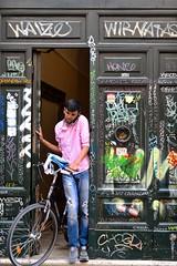 Graffiti door (jeremyhughes) Tags: rome door graffiti man bike bicycle phone telephone mobilephone exit domestic italy city urban tagging tags street nikon d750 sigma 50mm 50mmf14 checkshirt checks chequered pink