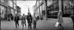 Walking the Walk [7] (*monz*) Tags: street people blackandwhite bw panorama woman man streets film church bag poster jack jones birmingham kodak iso400 candid trix 11 panoramic shops widelux hm vero f28 carrier shoppers bullring 9m brum 20c modo xtol f7 stmartinschurch 26mm monz panon
