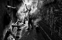 smoked morning (swarat_ghosh) Tags: street morning people blackandwhite india brick texture silhouette wall asian alley asia smoke streetphotography rays sunrays kolkata hoogly serampore yahoo:yourpictures=yourbestphotoof2012