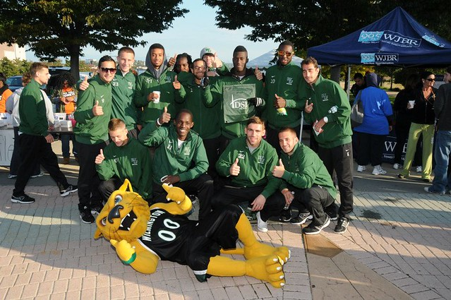 The men's soccer team takes a break with mascot Wiley D. Wildcat after walking in honor of Dr. Jim Wilson at the 5th Annual Kidney Walk at the Riverfront.