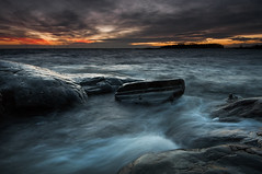 First sunset II (- David Olsson -) Tags: sunset lake seascape motion nature wet water clouds landscape flow movement nikon rocks waves sundown cloudy sweden tripod january dramatic vivid windy boulder cliffs filter colourful grad hitech vnern dx hammar vrmland windturbines 1635 metalring awash 1635mm lakescape gnd skoghall 2013 d5000 scenicsnotjustlandscapes davidolsson 09hard 1635vr grytudden