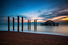(drfugo) Tags: sunset sea sky beach water clouds reflections twilight brighton waves dusk steel pebbles structure westpier burnt poles pillars remains urbex sigma28mmf18exdg canon5dmkii