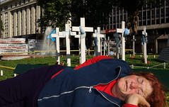 """Holidays in Buenos Aires: The People by Oscar_from_Denmark - At the background of this picture there are some banners and of course, the crosses.  At the time of the infamous Malvinas/Falkland War some Argentinian soldiers were sent to the islands to fight and some where ask to wait until it came their turn. It is this last group that is fighting for the right to be recognized as war veterans in spite that they never (really) fought.   One of the banners reads """"We did what we were asked for""""."""