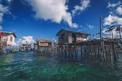 Houses with sea views... (Syahrel Azha Hashim) Tags: community nikon seagypsies tokina clearsky shallow holiday malaysia housesonstilts details dramaticsky ultrawideangle semporna sabah local dof poverty sunny denawanisland people clearwater boat clouds humaninterest handheld 11mm simple vacation residential children light unfortunate naturallight moment colorful beautiful d300s travel syahrel simplelife clothes ocean getaway family woodenboat tropical detail