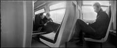 A Stolen Moment (*monz*) Tags: street blackandwhite bw panorama sun streets film train star newspaper birmingham chair couple sleep iso400 candid 11 device panoramic seal widelux headphones hp5 klingon ilford treck lager brum 20c xtol f7 12m 26mm cloaking monz panon autaut