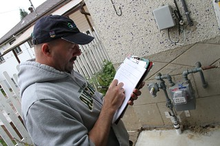 The energy auditor measures the exterior of th...