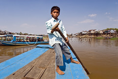 A young boy helps guide a boat on Tonle Sap Lake. (dkjphoto) Tags: travel boy lake fish tourism water river boat fishing asia cambodia seasia cambodian tour village tourist pole oar siemreap stilt tonlesap