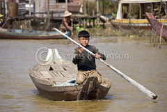 Young boy paddles a boat on river near Tonle Sap Lake. (dkjphoto) Tags: travel boy lake fish tourism home water river boat fishing asia cambodia seasia cambodian tour village tide paddle tourist siemreap stilt raised tonlesap