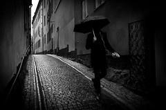Echoes Of Rain And Italian Shoes.. (Peter Levi) Tags: street city blackandwhite bw man blancoynegro monochrome umbrella 35mm mono alley sweden stockholm stones streetphotography documentary cobble gamlastan oldtown socialdocumentary paraply x100 fujifilmx100 finepixx100 fujix100