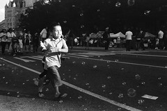 Bubbles (Eric Spiegel) Tags: road street boy blackandwhite film festival analog photography washingtondc dc kid child streetphotography bubbles pennsylvaniaavenue dcist 135 nikonfe soapbubbles streetfestival contaxt2 38mm fiestadc