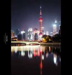 Pudong Lujiazui Skyline Reflections (Vertical) (Lao An (PhotonMix)) Tags: china longexposure urban vertical misty skyline architecture modern night reflections lights cityscape shanghai smooth illuminated led future tvtower jinmaotower highrises shanghaipudong orientalpearltower suzhoucreek swfc waibaidubridge shanghaiworldfinancialcenter pudonglujiazui flickraward5 photonmix laoanphotography