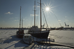 Frozen Harbour (Hartmann Photo) Tags: travel blue winter sea sky sun white snow blur reflection ice water sailboat port reflections poster photography pier sailing ship shadows background atmosphere vessel quay maritime bow transportation sail mast nautical sailboats starburst rstider