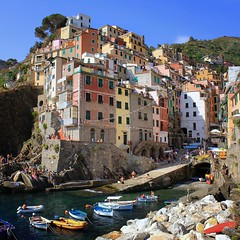 The tower houses look down on Riomaggiore's small harbor (B℮n) Tags: world ocean park pink flowers blue trees houses sea summer vacation sky orange sun sunlight holiday flower tower heritage water colors beautiful weather train buildings walking coast boat high warm mediterranean italia sailing ship torre gulf hiking path five character liguria shoreline hike case cliffs lovers quay historic unesco via vineyards national wharf terre sail botanic mountainside overlooking quaint inspire incredible viewpoint picturesque coloured trial cinque adriatic riomaggiore italianriviera torri yellew dellamore guardiolas