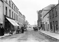 Market Street, Mountmellick (National Library of Ireland on The Commons) Tags: ireland car awning automobile donkey bank bowlerhat posters shops lawnmower sack marketstreet rugs bonnet eason quaker wheelbarrow brooms pawnbrokers bsa glassnegative pratts hsmith telegraphwires motorcar braymer telegraphpoles leinster laois lombards mountmellick queenscounty pawnshops cokehat patrickmalone nationallibraryofireland motorspirit nectartea spiritstores bsabicycles humphrysmith easonson easoncollection angloamericanoilco hsmithsons cfoy patricktalbotmalone bideliamalone ln3844