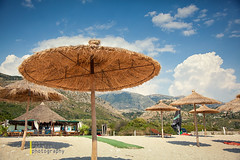 straw parasol at a beach in southern Albania (azem) Tags: blue sea summer vacation tourism beach sunshine umbrella canon relax eos sand straw sunny hut parasol 5d balkans relaxation albania idyllic chill 2012 sunbed chillout markii ionian