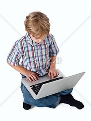 high angle view of a blonde boy using laptop (peoplebeck2012) Tags: boy cute male childhood computer photography portable sitting technology child laptop web internet innocent fulllength adorable indoors whitebackground elearning learning studioshot wirelesstechnology browsing caucasian legscrossed casualclothing colorimage highangleview oneboyonly 67years elementaryage informationmedium