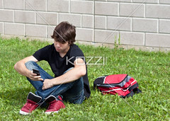 teenage boy reading a text message (elisapeople2012) Tags: boy male wall modern bag photography reading student holding education portable day sitting technology phone fulllength cellphone handsome lifestyle communication teenager network wirelesstechnology typing connection textmessage oneperson lookingaway texting caucasian schoolbag youthculture legscrossed casualclothing colorimage universitystudent oneboyonly portabledevice builtstructure oneteenageboyonly legscrossedatankle personineducation 1516years secondaryschoolchild teenageronly
