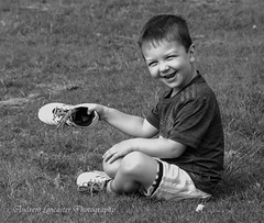 Frazier I lost my football boot (Andrew Lancaster photography) Tags: boy portrait football black white happy smile