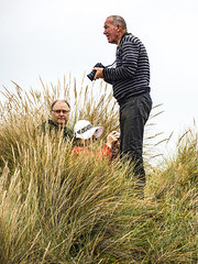 Getting a Close Up (Steve Taylor (Photography)) Tags: camera photographer strap hat glasses looking juxtaposition closeup fun man men woman lady newzealand nz southisland canterbury christchurch newbrighton dune grass cloud