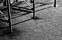 Under the Pier (Leonie Carr) Tags: bridge shadow bw white abstract black reflection texture beach water monochrome pier seaside interesting sand long noir pattern salt shapes beam ridge cast elements shape et blanc beams element