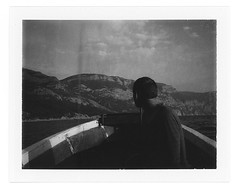 Stranger on the boat (Andrey Timofeev) Tags: sky sun mountains clouds analog landscape polaroid person boat horizon analogue crimea landcamera          polaroidcolorpackiii fujifilmfp3000b balaklavabay 01102 instantblackwhitefilm  03oct2012