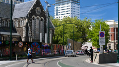 Up the Wall He Goes (Jocey K) Tags: trees newzealand christchurch sky people signs church architecture clouds buildings skateboarding tramlines earthquakedamagedchristchurchcathedral cathdedralsq