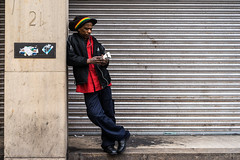 Lean Times (Cliff.j) Tags: rasta hat glasgow street leaning lean candid city closed shop front shutter pillar colour step phone smoking man bank earphones cargo trousers sony mirrorless entrance carl zeiss sonnar 55mm a7