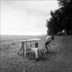 (Kenneth McNeil) Tags: africa bw 6x6 film beach water girl analog zeiss mediumformat square table grey chair alone peace kodak tmax empty hasselblad 400 squareformat carl serenity sit 500c medium format isolation serene tmax400 emptiness kodaktmax400 mozambique maputo planar 80mm carlzeiss costadosol hasselblad500c planar80mm kennethmcneil