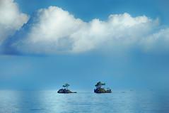 Twin Rocks 2 (Collin Key) Tags: blue bomba ocean soft clouds sulawesi togianislands rocks sky texture boats indonesia solitarytrees sea idn