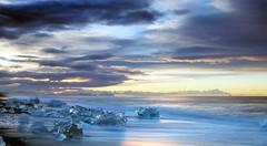 musing on ice and fire ... (lunaryuna) Tags: iceland southeasticeland coast shoreline northatlantic blackvolcanicbeach glacialice glacialicefloes diamondbeach jokulsarlon sunrise dawn sky clouds lightmood spring season seasonalwonders lunaryuna ngc