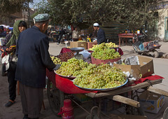 Man Selling Grapes, Kashgar,  Xinjiang Uyghur Autonomous Region, China (Eric Lafforgue) Tags: china street travel people man tree tourism horizontal outside person kid day outdoor muslim chinese citylife stall banana mobilephone uighur xinjiang silkroad kashgar daytime uyghur date rearview cart minority kashi grape foodanddrink youngwoman anthropology ethnicity sociology whitecap peoplesrepublicofchina autonomy dayview turkic 3people humanright uygur threepeople ouigour colorpicture threepersons unrecognizablepeople doppi ethnicgroup chineseturkestan img9508 kachgar unrecognizableperson colourpicture xinjianguyghurautonomousregion easternandcentralasia turkicethnicgroup countycitylevel qeåqer doppilar araxcin
