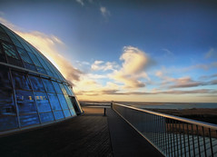 On Top of the Perlan in Reykjavik, Iceland (` Toshio ') Tags: winter sunset sky cloud sun sunlight cold building water glass architecture clouds restaurant bay iceland cafe europe european rail reykjavik deck pearl perlan icelandic toshio