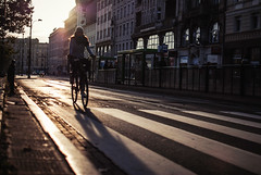 The rush of not going anywhere fast. (ewitsoe) Tags: ewitsoe nikond80 35mm street urban city bike woman lady poland poznan europe light sunrise cityscape bicycle