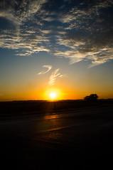thanksgiving eve sundown (Real Cowboys Drive Cadillacs) Tags: road blue sunset sky orange sun sunlight tree field silhouette yellow clouds landscape cowboy texas unitedstates farm country cadillac sunburst asphalt baycity mygearandme
