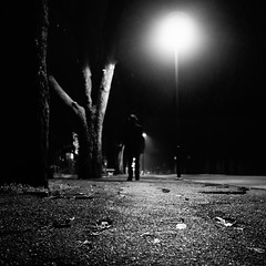 noir city (i k o) Tags: street city autumn trees blackandwhite man motion hat leaves foglie alberi night dark walking geotagged strada noir mood dof sony highcontrast evil lonely pancake alpha cinematic 16mm autunno atm