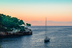 Early morning (marionrosengarten (off for holidays)) Tags: calaferrera mallorca spanien spain balears sea ship mediterranean holiday sunrise morning early orange red colours sailingboat waves