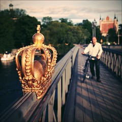 the Crown (*Kicki*) Tags: stockholm sweden skeppsholmen skeppsholmsbron man person bike bicycle bridge square crown gold 35mm amiralitetshuset bro fence city bokeh royal