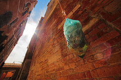 "hanging garbage bag (""Strlic Furln"" - Davide Gabino) Tags: garbage bag venezia venice sun sole walls muri muro wall brick mattone mattoni green orange sky cielo arancione case houses flare samyang14f28"