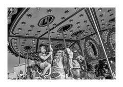 Carousel Rider, 2016 (marcolafou) Tags: bw blackandwhite candid car carnivalride carousel merrygoround midway monochrome newyorkstate perspective statefair street upstateny