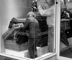 Searching for the best (farwest56) Tags: street uk england people blackandwhite bw woman man building glass shop umbrella shopping 50mm mono couple cornwall sony truro searching a350 sal50f14