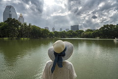 bangkok (Roberto.Trombetta) Tags: asia thailand bangkok lumphini park lake water garden hat girl loneliness lone cloudy storm building landscape view sonyalpha sony7rii sony7rmii batis225 carlzeiss zeiss carl sony alpha 7rii lenses tree looking waiting melancholy people lifestyle fashion