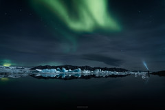 Descending Light (outofinsight) Tags: iceland northernlights auroraborealis sky night travel lake glacier lagoon ice iceberg jokulsarlon person torch camping silhouette reflection