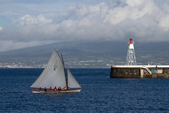Returning Whaler (Chris Haigh) Tags: whaler angustias harbour faial horta whaling hunting traditional sails pleasure chrishaigh 2016 azores portugal water lighthouse seawall pico mountpico clouds