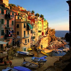 Riomaggiore where small boats go night fishing for anchovies (Bn) Tags: world ocean park flowers blue houses sunset sea summer vacation sky orange sun sunlight moon holiday tower heritage classic water colors beautiful weather night buildings walking boats coast boat high fishing topf50 warm mediterranean italia sailing ship torre gulf view hiking path five liguria shoreline hike case cliffs lovers quay historic unesco via anchovies national wharf terre sail botanic quaint viewpoint picturesque coloured topf100 topf200 cinque adriatic riomaggiore italianriviera torri dellamore 100faves 50faves 200faves guardiolas
