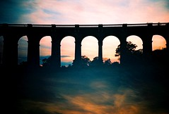 bridge in the sky (fotobes) Tags: bridge trees sunset sky silhouette clouds sussex lca xpro doubleexposure crossprocess railway viaduct multipleexposure valley balcombe kodakelitechrome100 balcombeviaduct ousevalleyviaduct splitzer